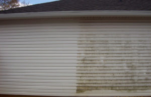 pressure washing siding on a house